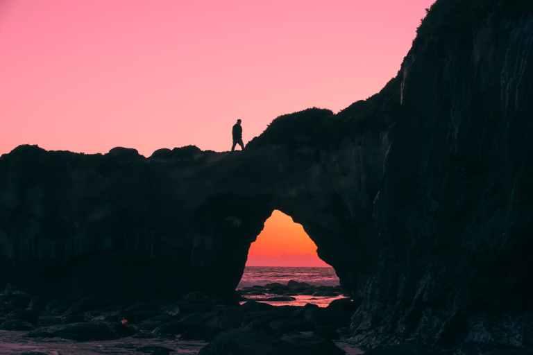 silhouette of man on rock walking during nightime